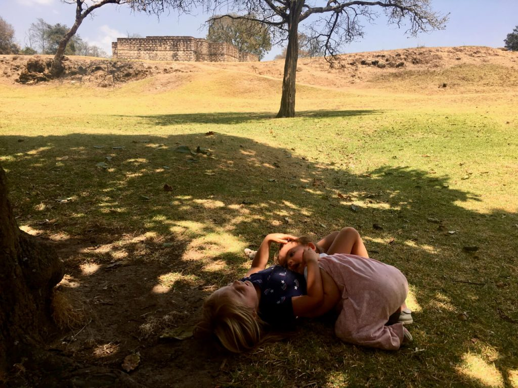 Two girls lying down in the shade.