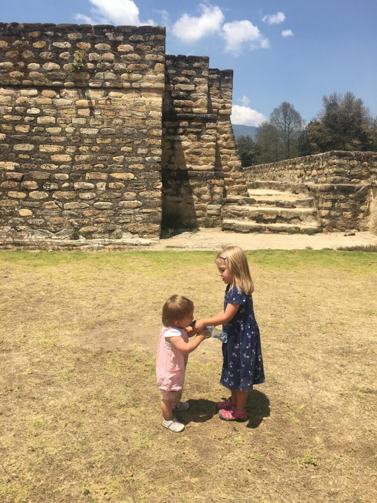 Two girls standing next to some ruins drinking a bottle of water
