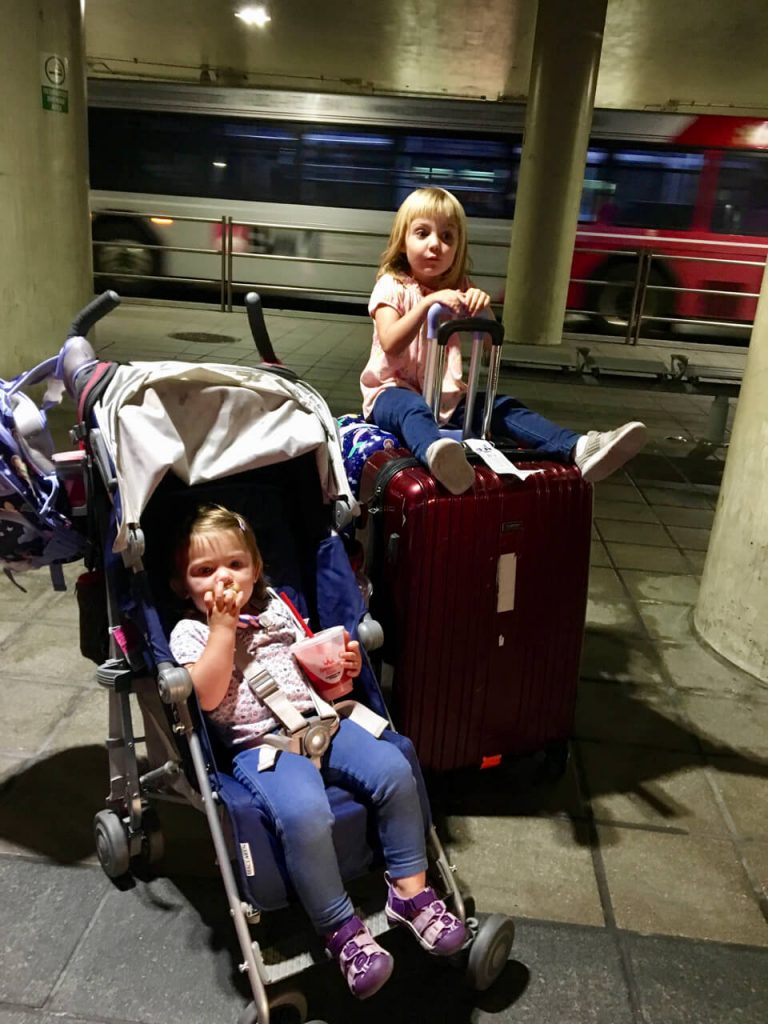 A kid on a suitcase, and a kid in a stroller at the airport.
