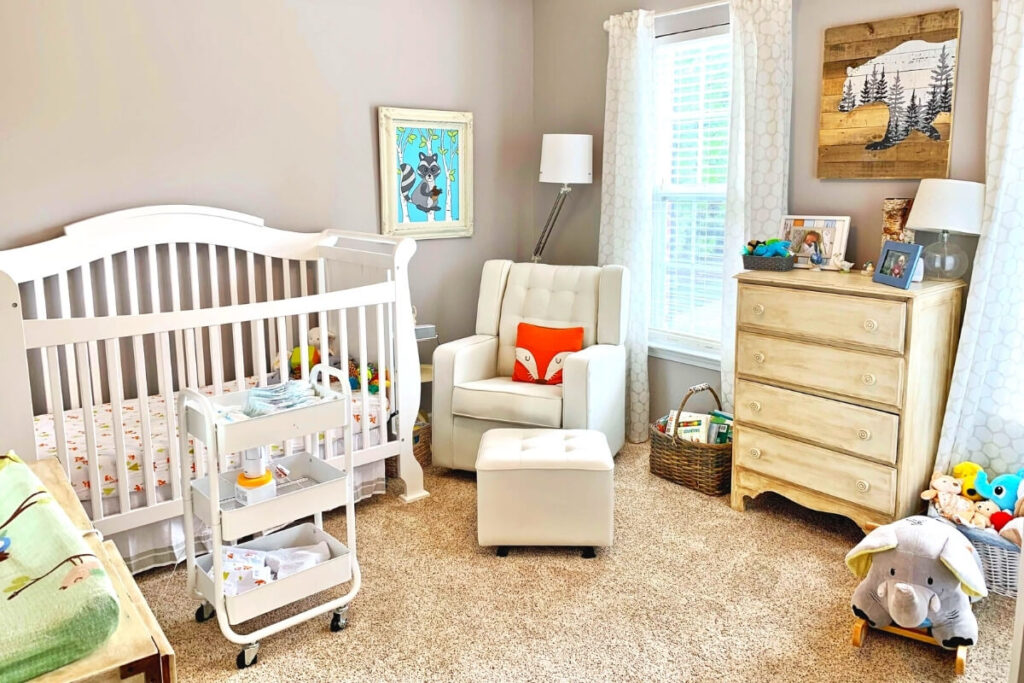 budget baby nursery showing cot, arm chair, ottoman, four chests of drawers, three tier trolley