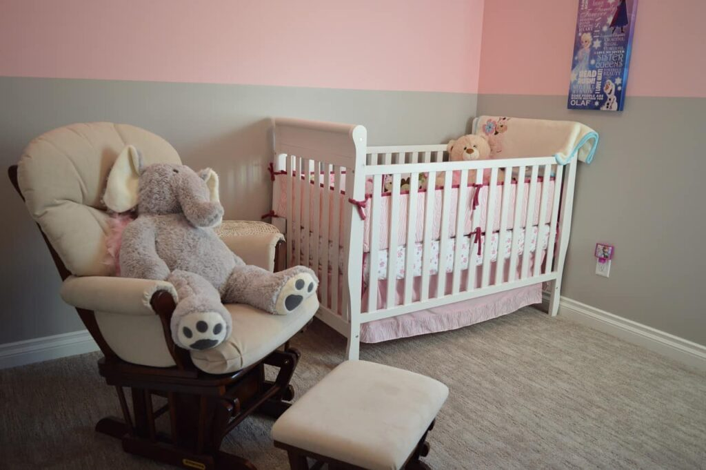 Cheap nursery glider with an elephant teddy sitting on it, and a white baby cot with a teddy in it